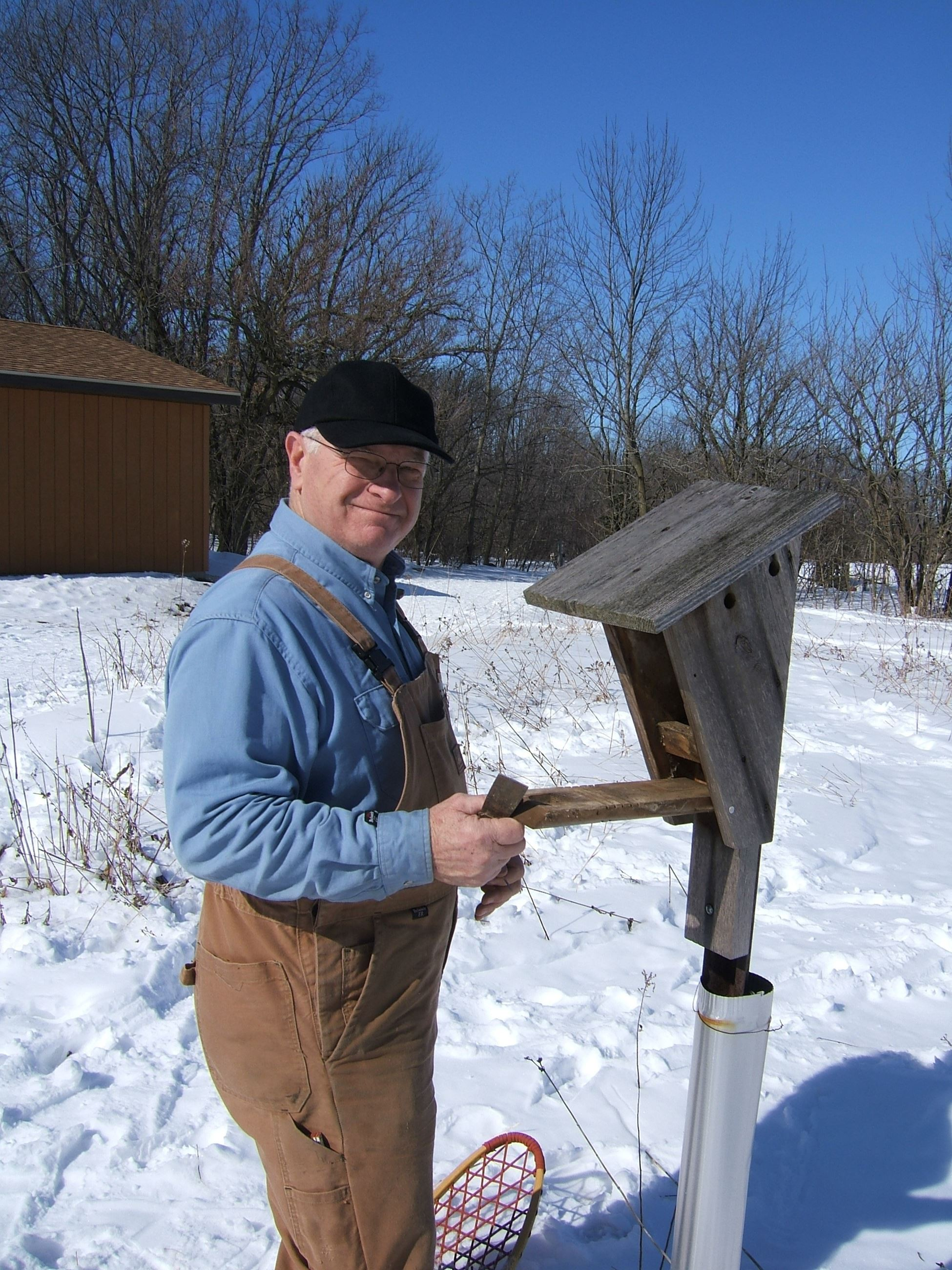 a picture of a man next to a bluebird house