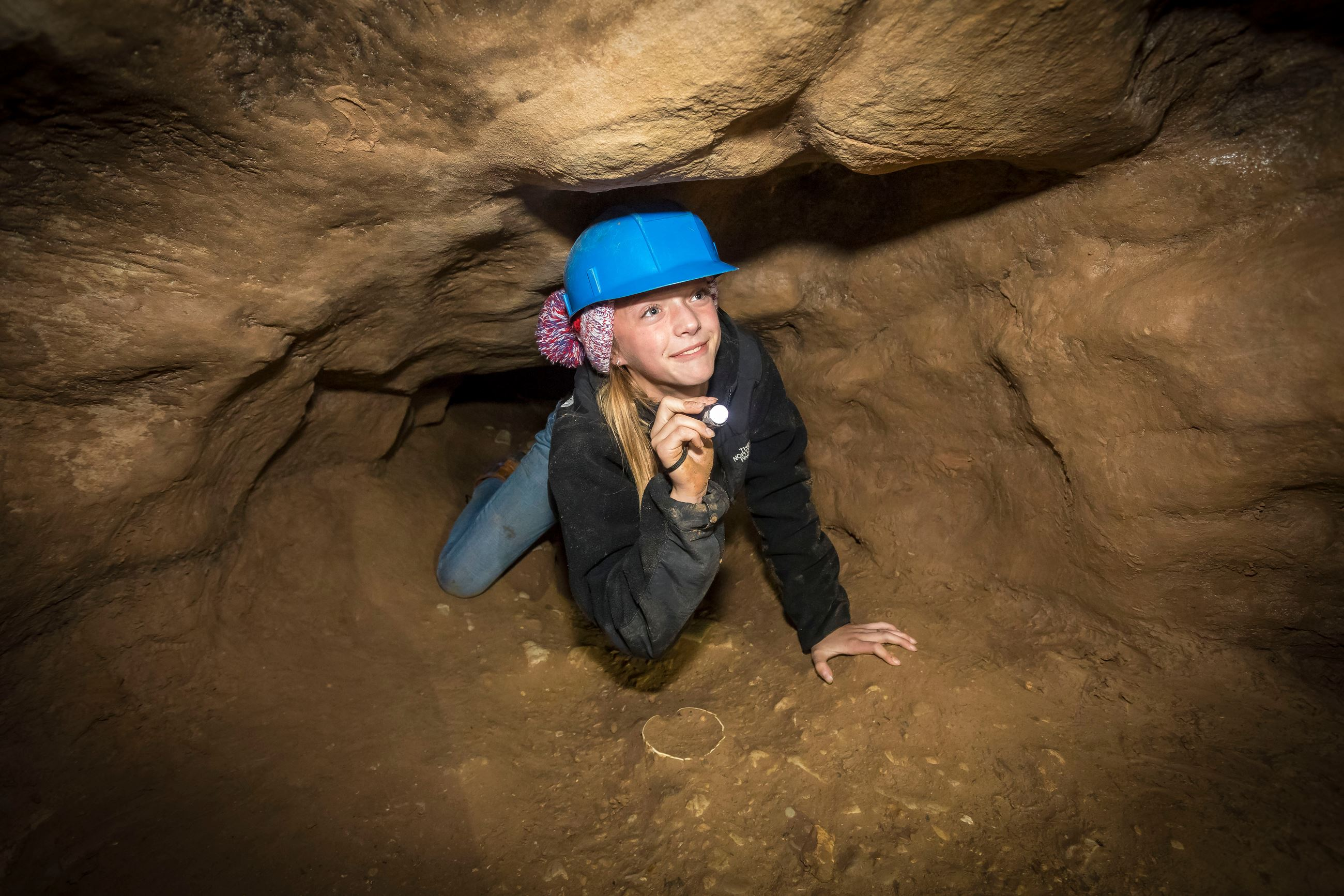 A girl wearing a blue helmet and holding a flashlight is crawling on her hands and knees through a t